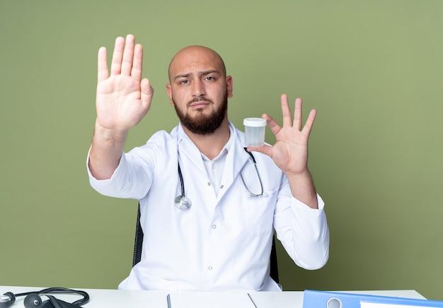 책상 작업에 앉아 의료 가운과 청진기를 입고 엄격한 젊은 대머리 남성 의사