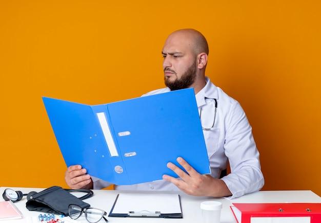 의료 가운과 청진기를 착용하고 의료 도구를 들고 오렌지 배경에 고립 된 폴더를보고 작업 책상에 앉아 엄격한 젊은 대머리 남성 의사