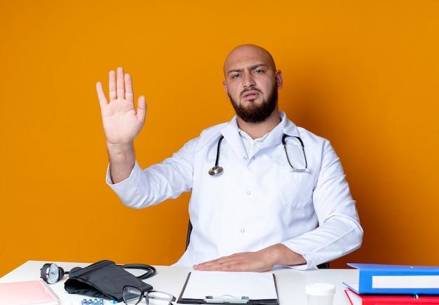 오렌지 벽에 고립 된 중지 제스처를 보여주는 의료 도구와 작업 책상에 앉아 의료 가운과 청진기를 입고 엄격한 젊은 대머리 남성 의사