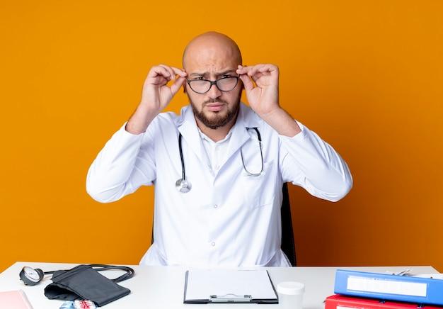 Il giovane medico maschio calvo rigoroso che porta veste medica e lo stetoscopio che si siedono allo scrittorio di lavoro con gli strumenti medici assumono i vetri sull'arancio