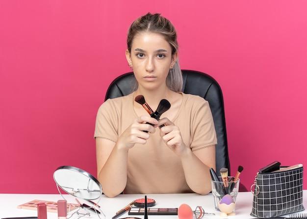 厳格な若い美しい少女は、ピンクの背景に分離されたパウダーブラシを保持し、交差する化粧ツールでテーブルに座っています。