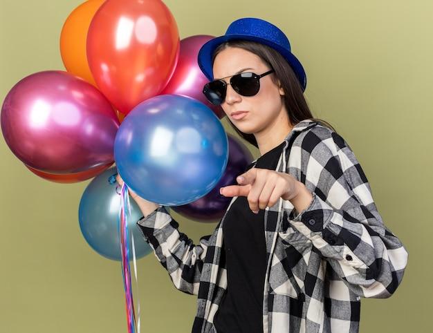 Rigorosa giovane bella ragazza che indossa un cappello blu con gli occhiali che tengono i punti di palloncini isolati sulla parete verde oliva