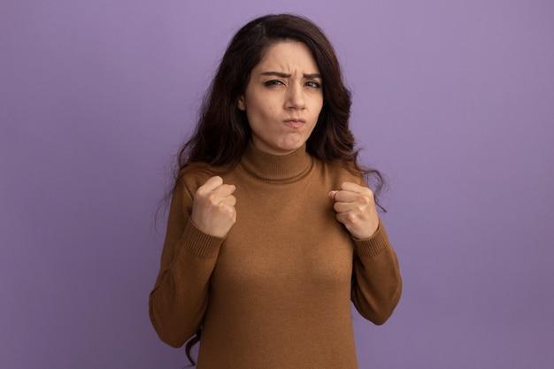 紫の壁に拳を保持している茶色のタートルネックのセーターを着ている厳格な若い美しい女の子