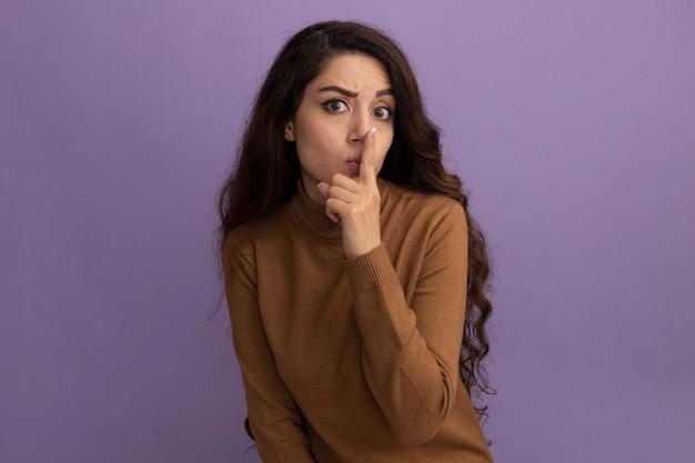 보라색 벽에 고립 된 침묵 제스처를 보여주는 갈색 터틀넥 스웨터를 입고 엄격한 젊은 아름 다운 소녀