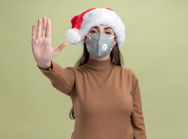 オリーブグリーンの背景に分離された停止ジェスチャーを示す医療マスクとクリスマスの帽子をかぶって厳格な若い美しい少女