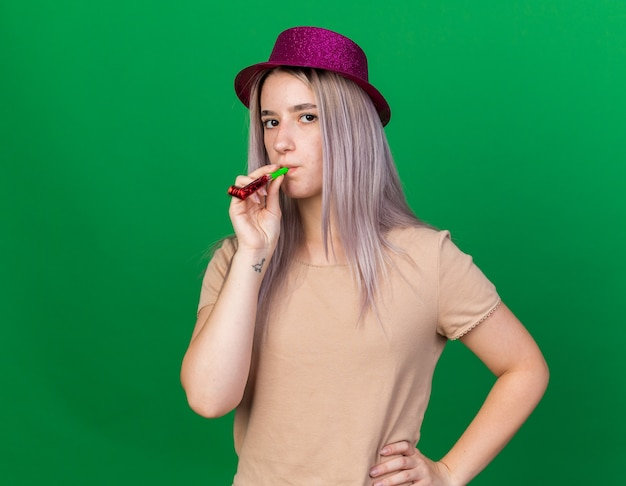 Strict young beautiful girl wearing party hat blowing party whistle putting hand on hip