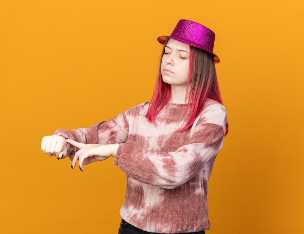 Strict young beautiful girl wearing party hat showing wrist clock gesture isolated on orange wall