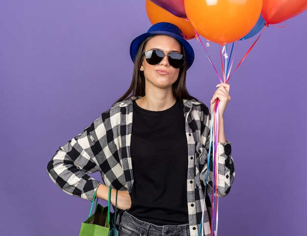 Strict young beautiful girl wearing party hat with glasses holding balloons putting hand on hip