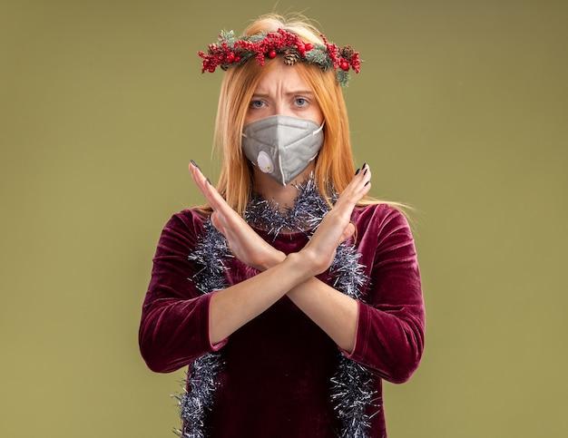 花輪と医療マスクと首に花輪の赤いドレスを着て、オリーブグリーンの背景に孤立していないジェスチャーを示す厳格な若い美しい少女