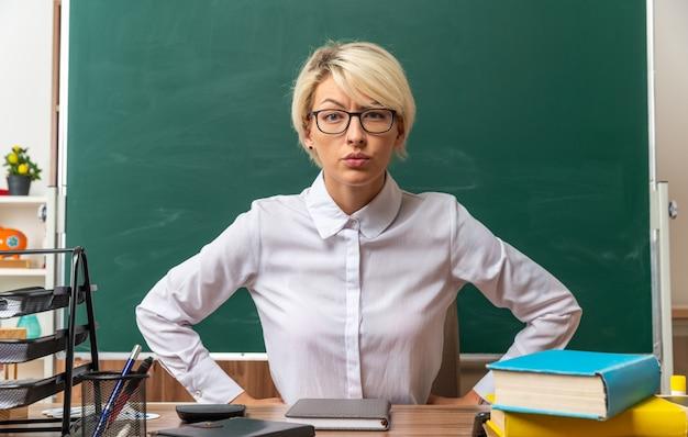 Строгая молодая блондинка учительница в очках сидит за столом со школьными принадлежностями в классе, держа руки на талии, глядя вперед