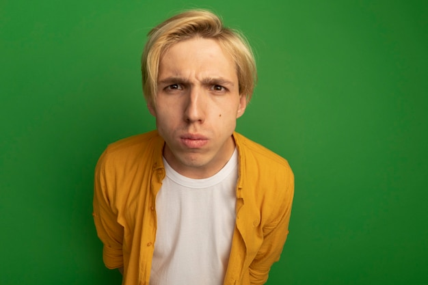 Strict young blonde guy wearing yellow t-shirt isolated on green with copy space