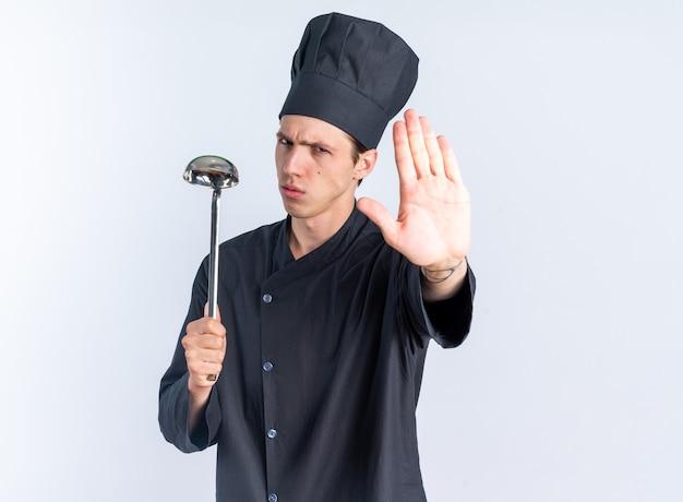 Cuoco maschio giovane biondo rigoroso in uniforme da chef e tappo che tiene mestolo guardando la telecamera facendo gesto di arresto isolato sul muro bianco con spazio copia