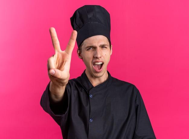 Cuoco maschio biondo rigoroso in uniforme da chef e berretto che guarda la telecamera urlando mostrando due con la mano isolata sulla parete rosa