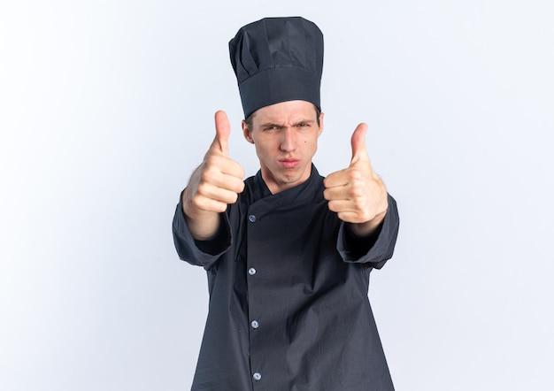 Cuoco maschio biondo rigoroso in uniforme da chef e berretto che guarda l'obbiettivo che mostra i pollici in su isolato sul muro bianco