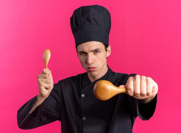 シェフの制服と帽子を持ってカメラに向かって木のスプーンを伸ばして伸ばしている厳格な若いブロンドの男性料理人