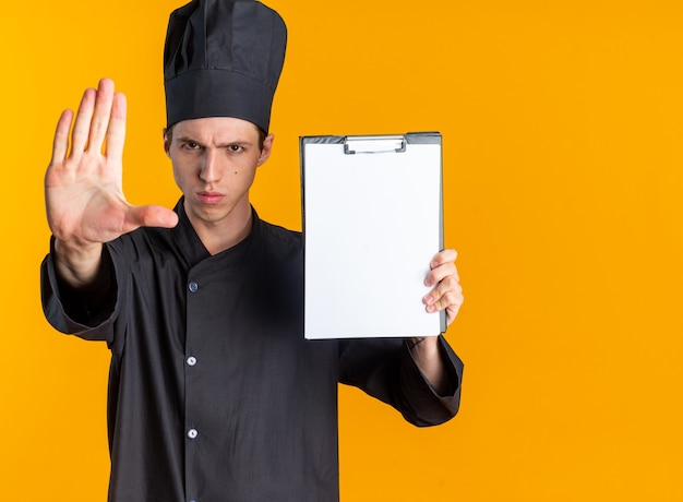 Строгий молодой блондин мужчина-повар в униформе и кепке шеф-повара смотрит в камеру, показывающую буфер обмена, делающий стоп-жест, изолированный на оранжевой стене с копией пространства