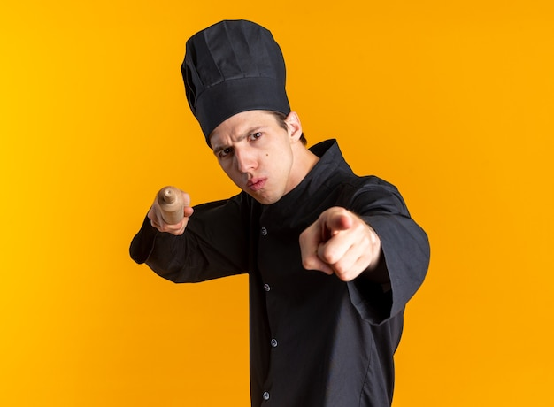 엄격한 젊은 금발 남성 요리사 유니폼을 입고 프로필 보기에 서 있는 모자와 롤링 핀과 손가락이 주황색 벽에 격리된 카메라를 가리키고 있습니다.