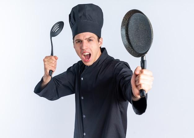 Строгий молодой блондин мужчина-повар в униформе шеф-повара и кепке, стоящий в профиле, глядя на камеру, держащую и протягивающую лопатку и сковороду, изолированные на белой стене