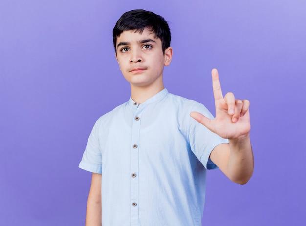 Rigoroso giovane ragazzo guardando dritto facendo gesto perdente isolato sulla parete viola