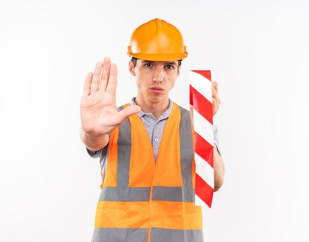 Rigoroso giovane costruttore in uniforme che tiene del nastro adesivo che mostra il gesto di arresto isolato sul muro bianco