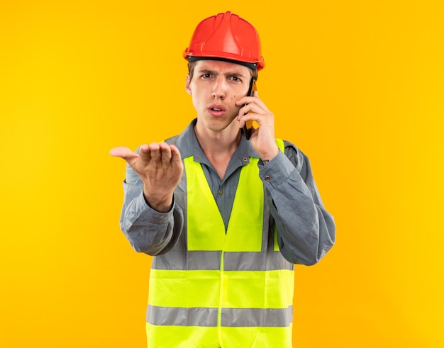 Strict young builder man in uniform speaks on phone holding out hand at camera