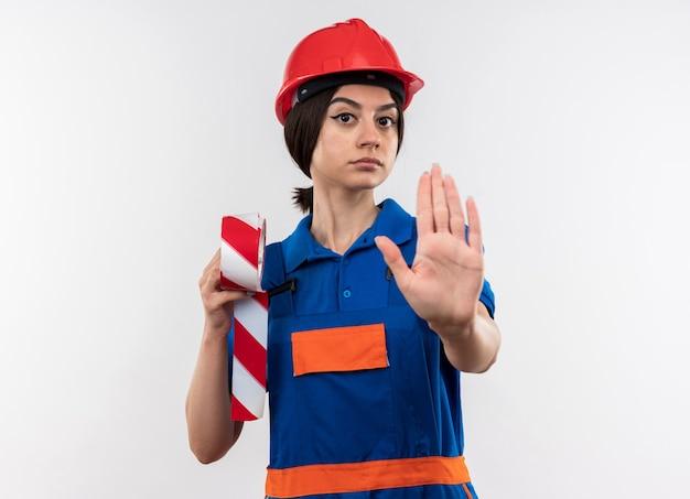 중지 제스처를 보여주는 덕트 테이프를 들고 제복을 입은 엄격한 젊은 건축업자 여자