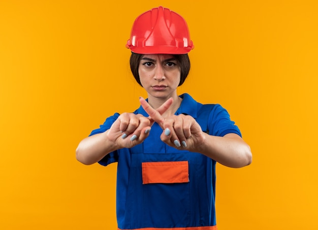 Strict young builder woman in uniform showing gesture of no isolated on yellow wall