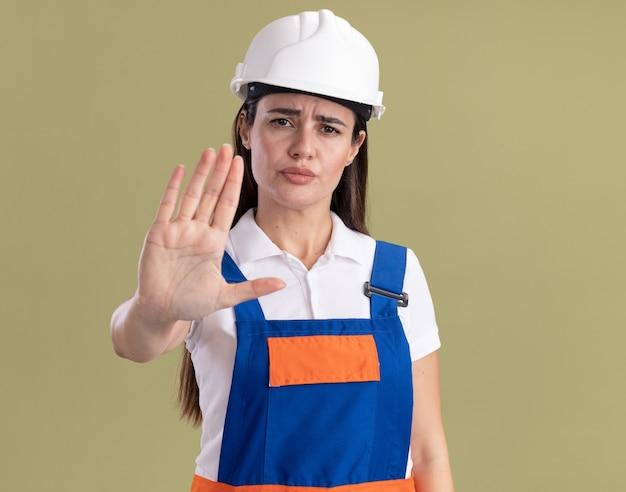Rigorosa giovane donna del costruttore in uniforme che mostra il gesto di arresto isolato sulla parete verde oliva