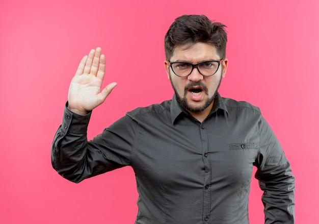 Строгий молодой бизнесмен в очках показывает жест стоп, изолированные на розовой стене