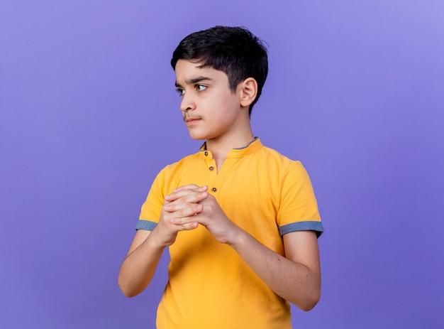 コピースペースと紫色の背景で孤立した手を一緒に保つ側を見ている厳格な若い白人の少年