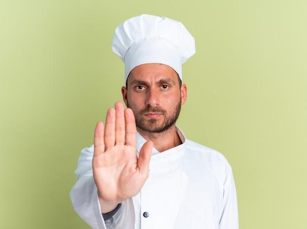 Строгий молодой кавказский повар в униформе и кепке шеф-повара смотрит в камеру и делает стоп-жест, изолированный на оливково-зеленой стене