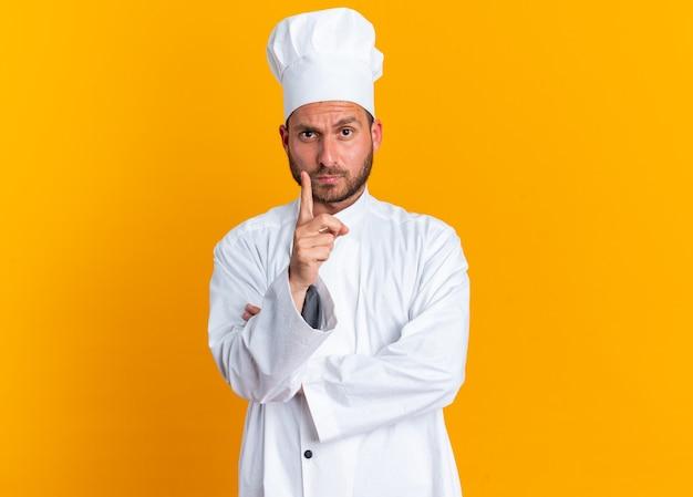 Строгий молодой кавказский повар в униформе шеф-повара и поднимающий кепку палец