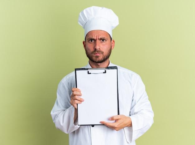 Строгий молодой кавказский мужчина-повар в униформе шеф-повара и кепке показывает буфер обмена, смотрящий в камеру, изолированную на оливково-зеленой стене