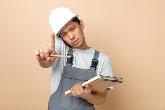 Strict young construction worker wearing safety helmet and uniform holding notepad and pencil doing hold on gesture