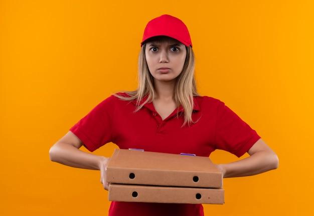 Rigorosa giovane ragazza di consegna che indossa l'uniforme rossa e il cappuccio che tiene la scatola della pizza isolata sulla parete arancione