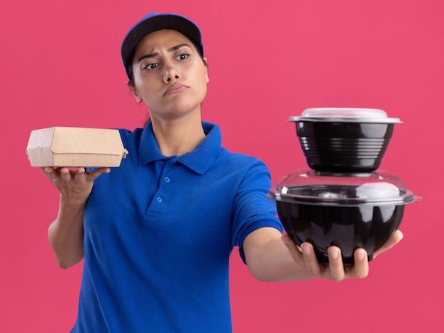 Rigorosa giovane ragazza di consegna che indossa l'uniforme con il cappuccio che tiene fuori i contenitori per alimenti isolati sulla parete rosa