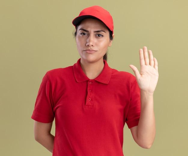 Строгая молодая доставщица в униформе с кепкой показывает жест стоп, изолированную на оливково-зеленой стене