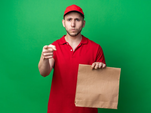 Strict young delivery guy wearing uniform with cap holding paper food bag points at front