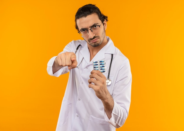 聴診器が丸薬を保持し、黄色のジェスチャーを示す医療ローブを身に着けている医療眼鏡をかけた厳格な若い医師