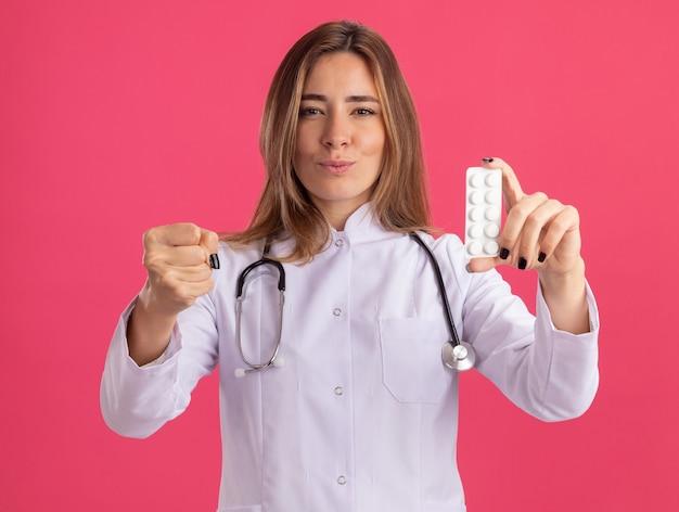 청진 기 약을 들고 분홍색 벽에 고립 된 주먹을 들고 의료 가운을 입고 엄격한 젊은 여성 의사