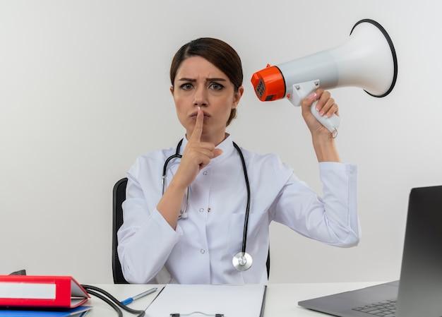 スピーカーを保持し、孤立した白い壁に沈黙ジェスチャーを示す医療ツールとコンピューターで机の仕事に座っている聴診器で医療ローブを着ている厳格な若い女性医師