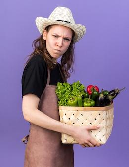 Rigorosa giovane giardiniere femminile che indossa un cappello da giardinaggio che tiene cesto di verdure