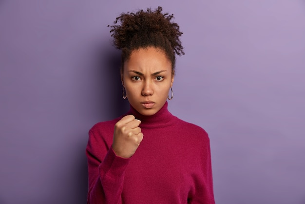 Strict young female teacher shows clenched fist , discontent with pupils behaviour, promises to punish, looks angrily, has curly combed hair, wears burgundy jumper, isolated on purple wall