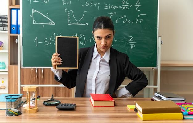 Severa giovane insegnante femminile si siede al tavolo con materiale scolastico tenendo mini lavagna in classe