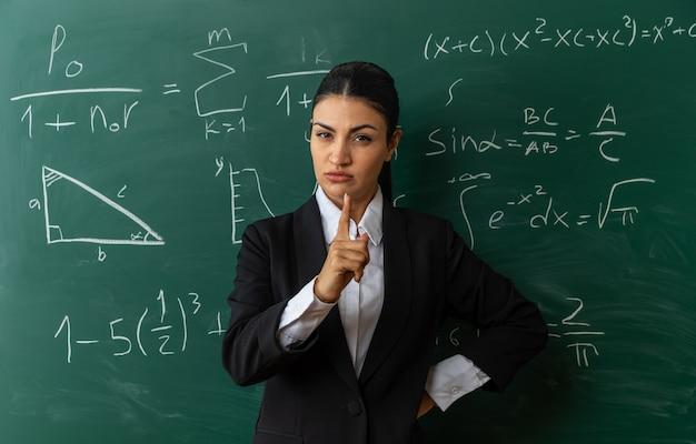 칠판 앞에 서 있는 엄격한 젊은 여성 교사는 교실에서 엉덩이에 손을 얹고 있다
