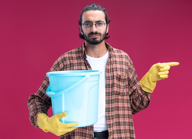 Strict young handsome cleaning guy wearing t-shirt and gloves holding bucket and points at side isolated on pink wall