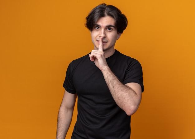 주황색 벽에 고립 된 침묵 제스처를 보여주는 검은 티셔츠를 입고 엄격한 젊은 잘 생긴 남자