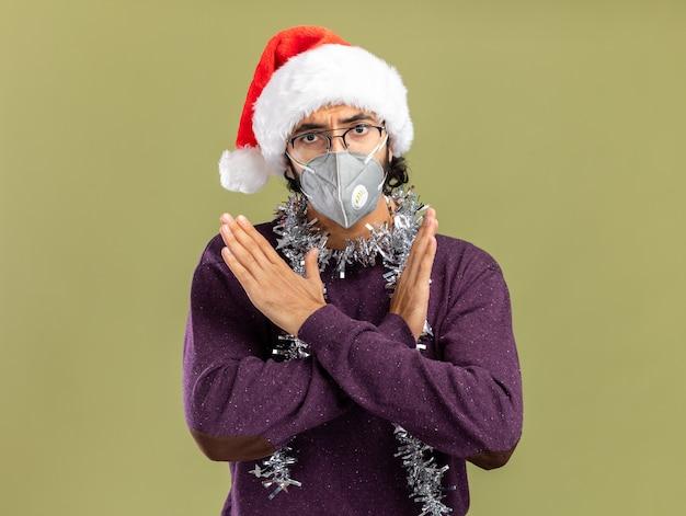 クリスマスの帽子と首に花輪とオリーブグリーンの背景に孤立していないジェスチャーを示す医療マスクを身に着けている厳格な若いハンサムな男