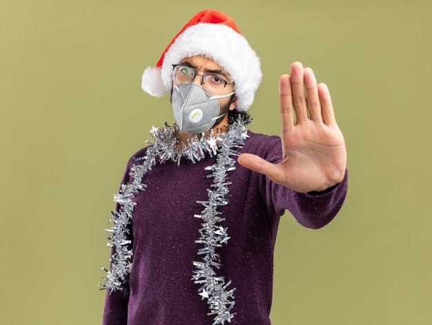 クリスマスの帽子と首に花輪とオリーブグリーンの背景で隔離の停止geestureを示す医療マスクを身に着けている厳格な若いハンサムな男