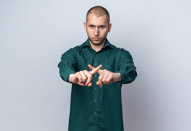Strict young handsome guy wearing green shirt showing gesture of no